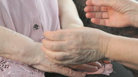 Woman strokes old woman`s hands during illness. Woman strokes the old wrinkled woman`s hands during a difficult illness. Close up stock footage