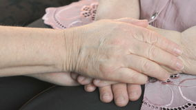 Woman strokes old woman`s hands in times of stress. Woman strokes the old wrinkled woman`s hands in times of stress. Close up stock video