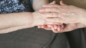 Woman strokes an old wrinkled woman's hand. During a difficult illness stock video footage