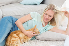 Woman stroking cat while playing with hair on rug Stock Images