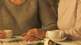 Woman stroking friend hand in support, two sisters experiencing grief together. Stock footage stock footage