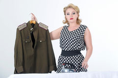 Woman stroking a military tunic. Blond woman stroking a military tunicn Royalty Free Stock Photo