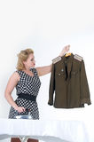 Woman stroking a military tunic. Blond woman stroking a military tunicn Royalty Free Stock Images