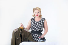 Woman stroking a military tunic. Blond woman stroking a military tunicn Stock Images