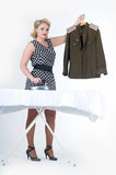 Woman stroking a military tunic. Blond woman stroking a military tunicn Stock Photo
