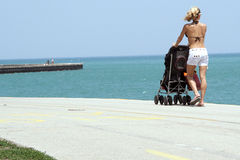 Woman with a stroller on beach Stock Images