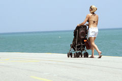 Woman with a stroller on beach stock photography