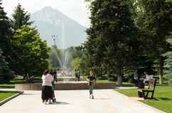 Woman with a stroller, a boy on a scooter. Almaty, Kazakhstan - 06.01.2018: Timiryazev street. people in the center of Almaty. Early summer time, woman with a Royalty Free Stock Images