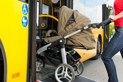 Woman with stroller getting into a bus. Young woman - only torso - with a baby in a stroller getting into a bus on the bus station Stock Images