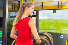 Woman with stroller getting into a bus Royalty Free Stock Images