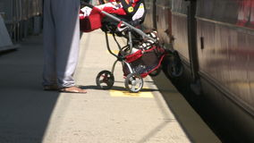 Woman with stroller getting onto train stock video