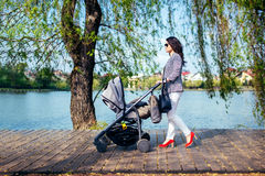 Woman with stroller on lake deck on city park. Happy mother walking child with pram stock photography