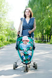 Woman with stroller  at summer park Stock Photography