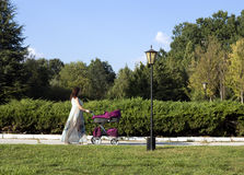 Woman with stroller. Walking in the park Stock Photos
