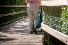 Woman With a Stroller on a Walkway on Blur Background at Turkey Creek, Niceville, Florida. Woman With a Stroller on a Walkway on Blur Background in Relax Time at royalty free stock image