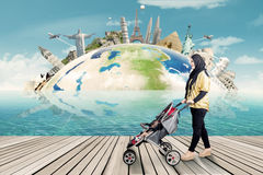 Woman with stroller and the world landmark Royalty Free Stock Images