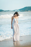 Woman strolling on beach in summer. Happy multiracial Asian girl going to sea. Woman strolling on beach in summer. Pretty happy multiracial Asian girl in white Royalty Free Stock Photo
