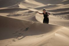 A woman strolling in sand dunes during sunset. stock photo