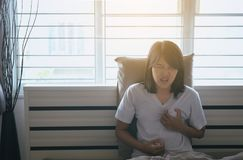 Woman with strong chest pain and hand touching her chest after wake up in morning,Heart attack symptom. Woman with strong chest pain and hands touching her chest stock photos