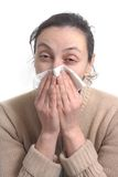 Woman with strong flu blowing her nose Stock Photography