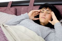 Woman with strong headache and fever lying in bed Royalty Free Stock Image