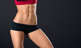 Woman with strong and perfect abs. Pretty woman's torso close up with strong and perfect abs on black background stock image