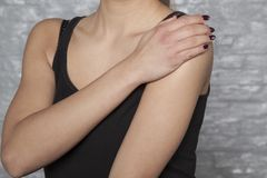 The woman is struggling with rheumatic shoulder pains. The woman is struggling with rheumatic, shoulder pains Stock Image