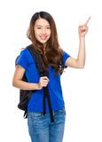 Woman student with backpack and finger point up Stock Image
