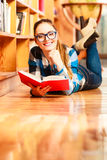 Woman student in college library. Education school concept. Casual female student fashionable girl in blue glasses lying on floor in college library with book Stock Photo