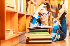 Woman student in college library. Education school concept. Clever female student girl in blue glasses lying on floor in college library with stack books reading Stock Images