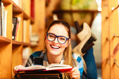 Woman student in college library. Education school concept. Clever female student girl in blue glasses lying on floor in college library with stack books reading Royalty Free Stock Photos