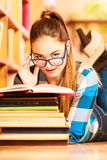 Woman student in college library. Education school concept. Clever female student girl in blue glasses lying on floor in college library with stack books reading Royalty Free Stock Images
