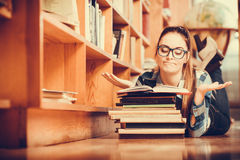Woman student in college library. Education school concept. Clever female student girl in glasses lying on floor in college library with stack books reading Stock Image