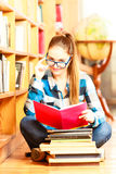 Woman student in college library. Education school concept. Clever female student hair ponytail girl blue glasses sitting on floor in college library with stack Royalty Free Stock Image