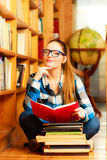 Woman student in college library. Education school concept. Clever female student long hair girl blue glasses sitting on floor in college library with stack Stock Images