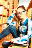 Woman student in college library. Education school concept. Clever female student long hair girl blue glasses sitting on floor in college library with stack Stock Photo