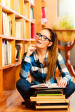 Woman student in college library. Education school concept. Clever female student long hair girl blue glasses sitting on floor in college library with stack Royalty Free Stock Image