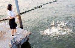 Woman student feeding fish at port Royalty Free Stock Photos