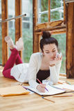Woman student, female artist, sitting on floor in college university drawing sketching Stock Photos