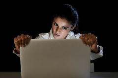 Woman or student girl working in darkness on laptop computer late at night holding the screen. Young business woman or student girl working in darkness on laptop Royalty Free Stock Images