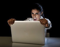 Woman or student girl working on laptop computer late at night holding the screen screaming Royalty Free Stock Images