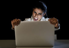 Woman or student girl working on laptop computer late at night holding the screen screaming Stock Photos