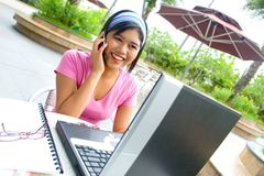 Woman student on her cellphone with an open laptop Royalty Free Stock Images