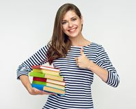 Woman student holding pile of book showing thumb up. Isolated studio portrait on white Royalty Free Stock Photography