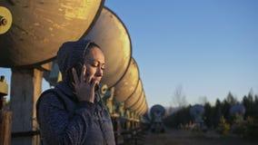 Woman student operator of institute of solar terrestrial physics talking on a cell phone. Unique array solar radio. Telescope. Sun Solar Radio Telescope. The ` stock video footage