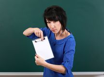 Woman student show blank paper sheet near chalk Board, education concept, green background, studio shot Royalty Free Stock Images