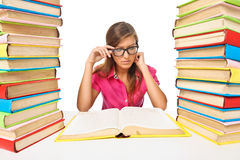 Woman student sitting at the desk surrounded with piles of books Royalty Free Stock Image