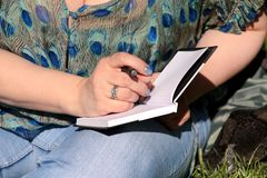 Woman and student sitting on grass, takes notes in notebook, learning and writes thoughts, writes book. Woman and student sitting on grass, takes notes in stock photography