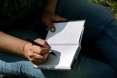 Woman and student sitting on grass, takes notes in notebook, learning and writes thoughts, writes book. Woman and student sitting on grass, takes notes in stock photo