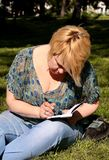 Woman and student sitting on grass, takes notes in notebook, learning and writes thoughts, writes book. Woman and student sitting on grass, takes notes in stock photos